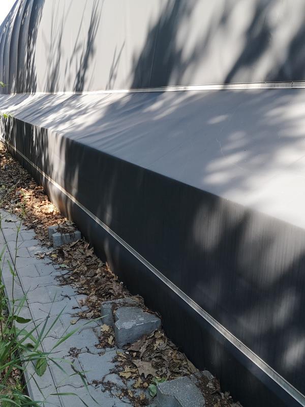 Hala tunelowa posadowiona na blokach betonowych - mocowanie fartucha